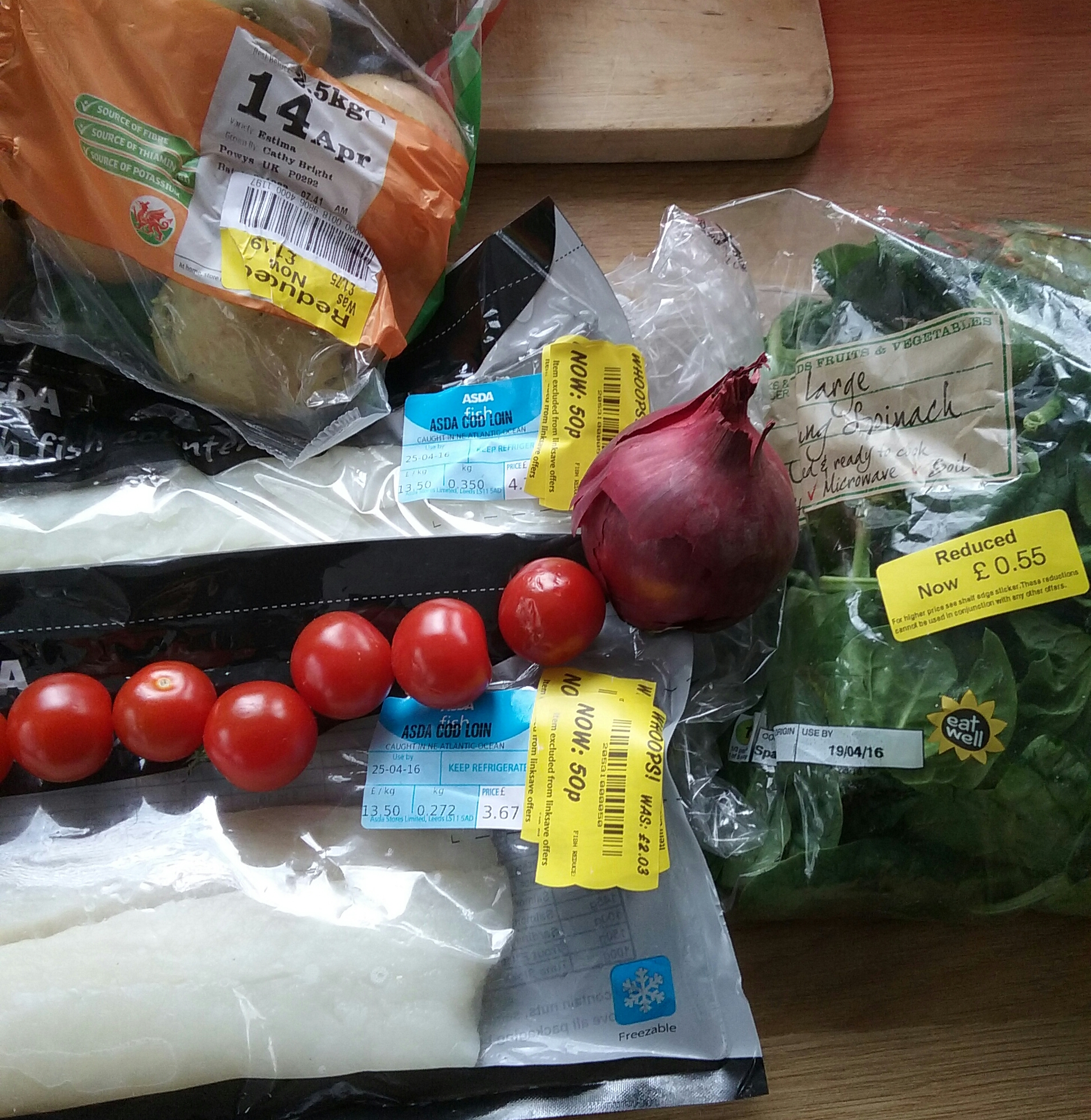 mix of ingredients, potatoes, spinach, tomatoes, red onions and cod (majority with yellow tags).