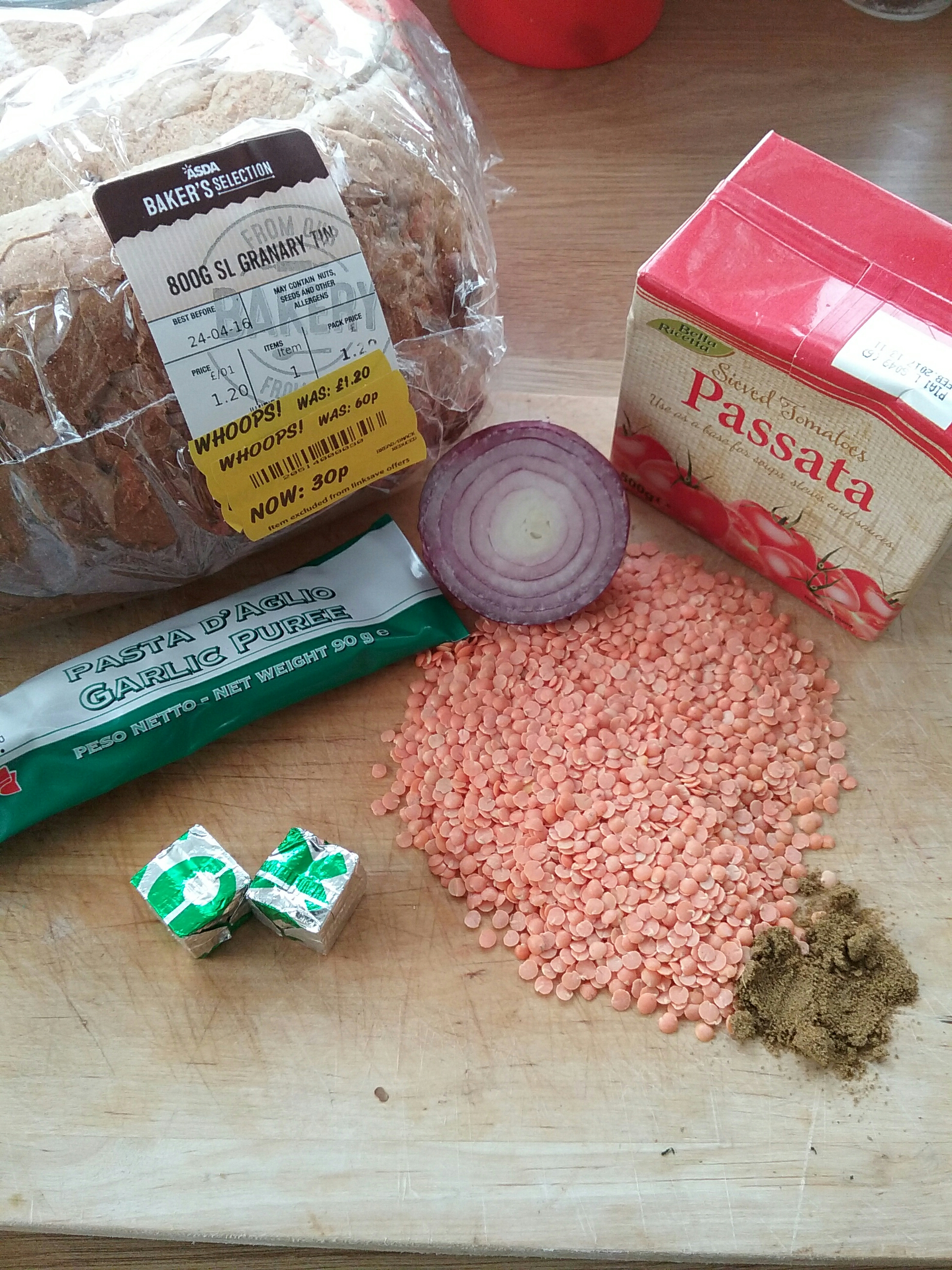 bread with yellow tag on a chopping board with lentils, red onion, passata sauce, garlic puree, herbs and stock cubes