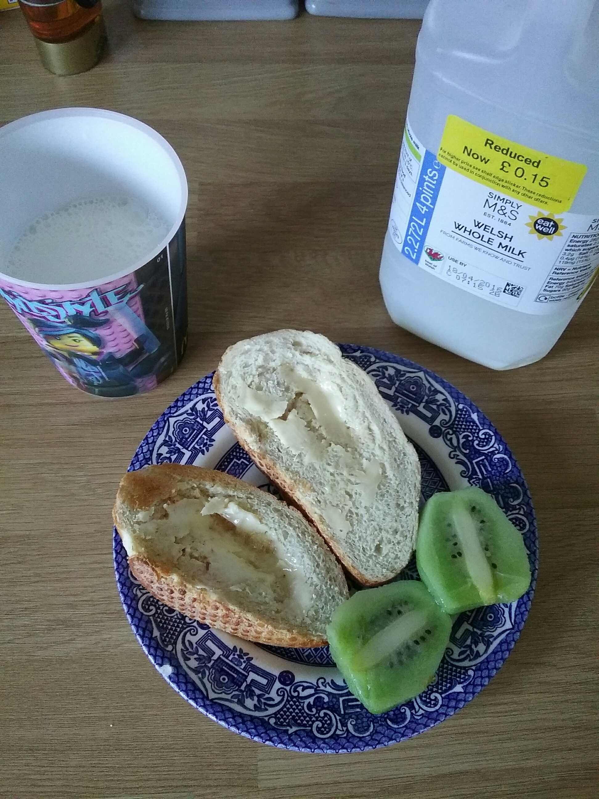 cup of milk alongside reduced whole milk with yellow ticket 15p and a blue plate of crusty bread and kiwi