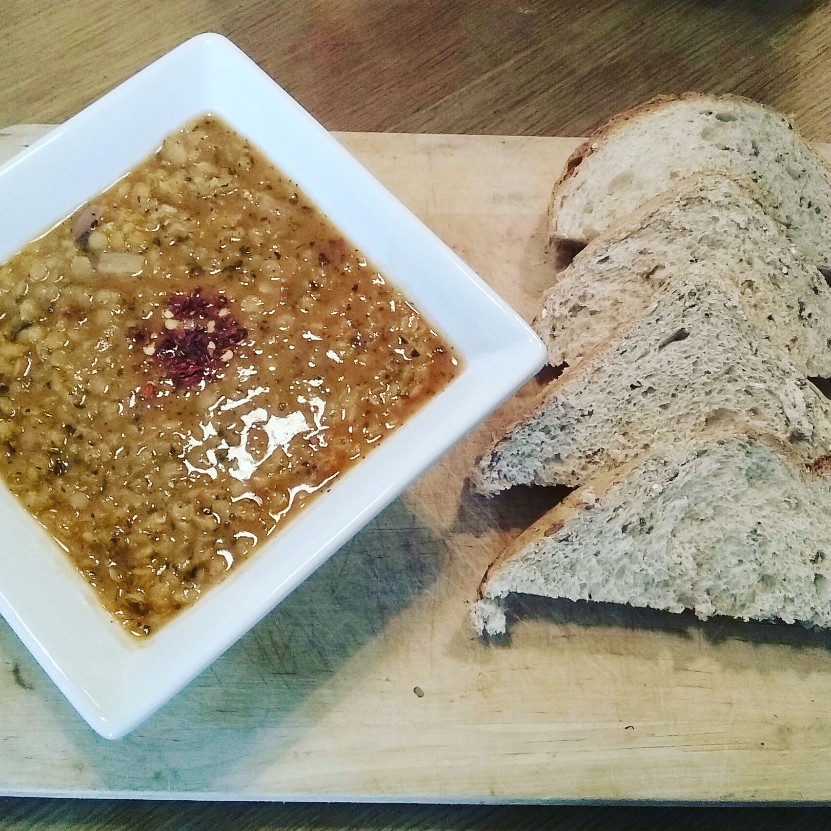 mercimet corba in a bowl alongside triangular cut bread on a chopping board