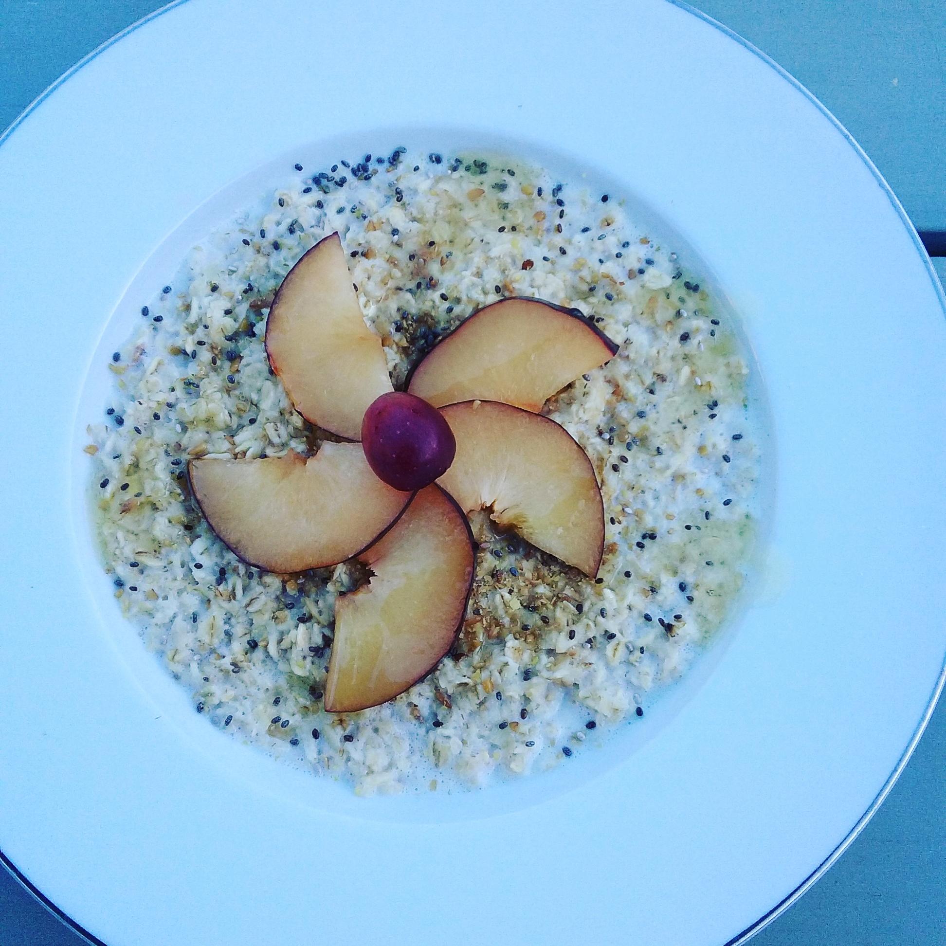 flatlay of porridge with plum and breakfast seeds